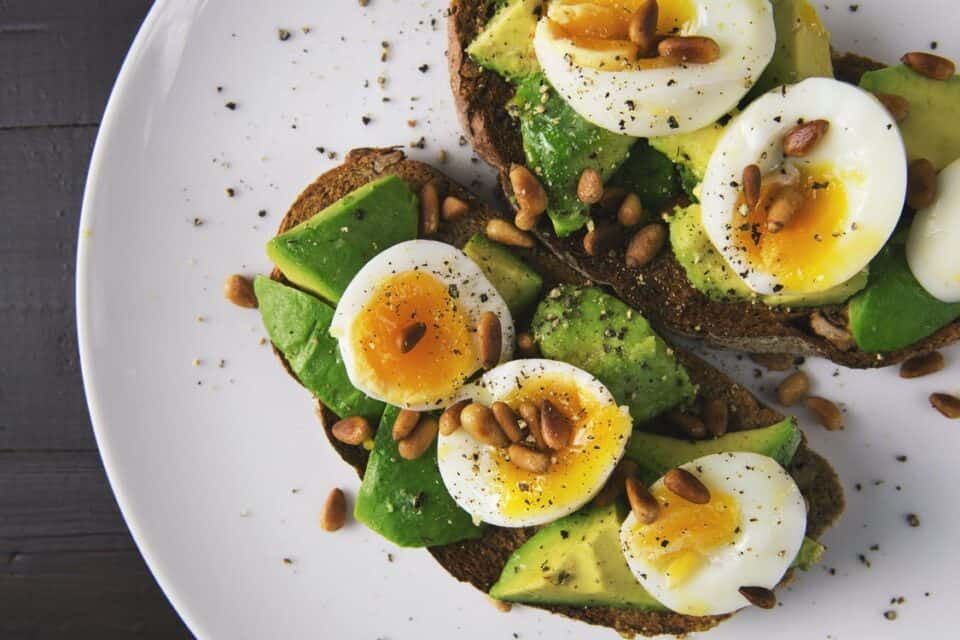Pastry, avocado and boiled egg on plate