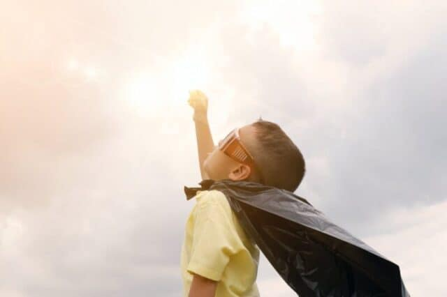 Benefits of exercise to children Boy rising up his hand wearing black cape