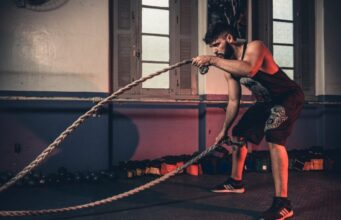 Man doing crossfit exercise with battle ropes indoor