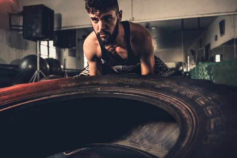 12 best weight loss activities Man lifting up a tire