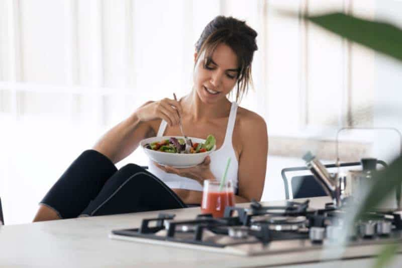 Sporty young woman eating salad and drinking fruit juice in the kitchen