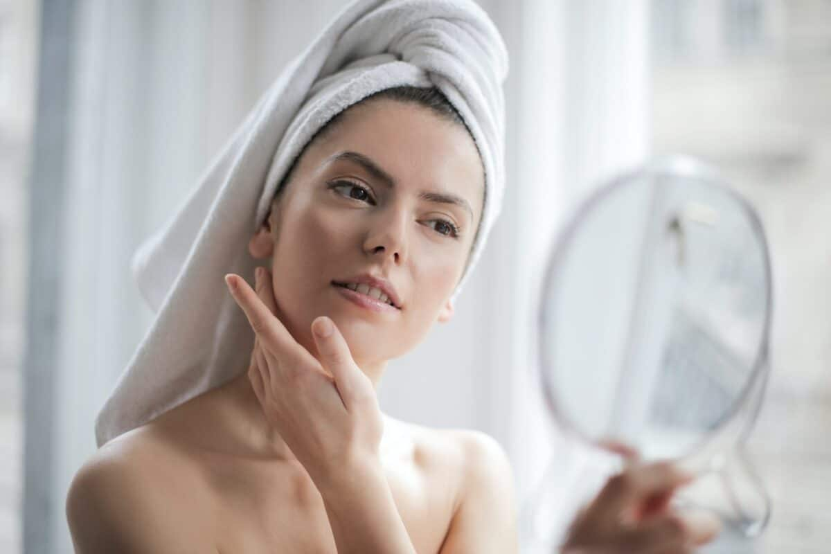 Woman with a towel on head looking in the mirror and nourishing the skin