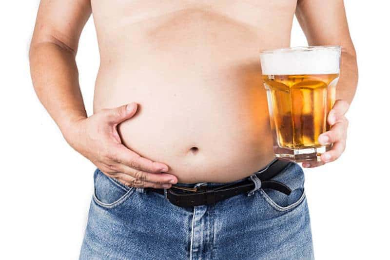 Obese man with big belly holding a glass of beer